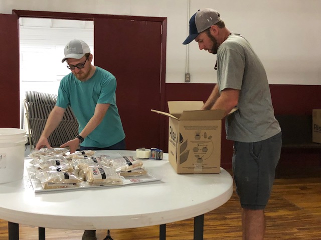 Volunteers package meals for the hungry